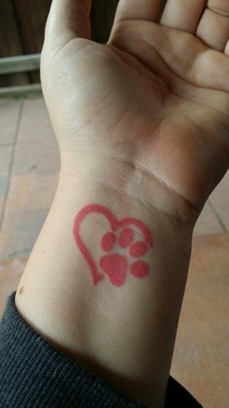 Tatuaje de huella de perro cerrando corazón en rojo