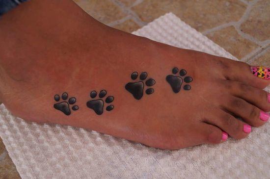 Tatuaje de huellas de perros sobre el pie