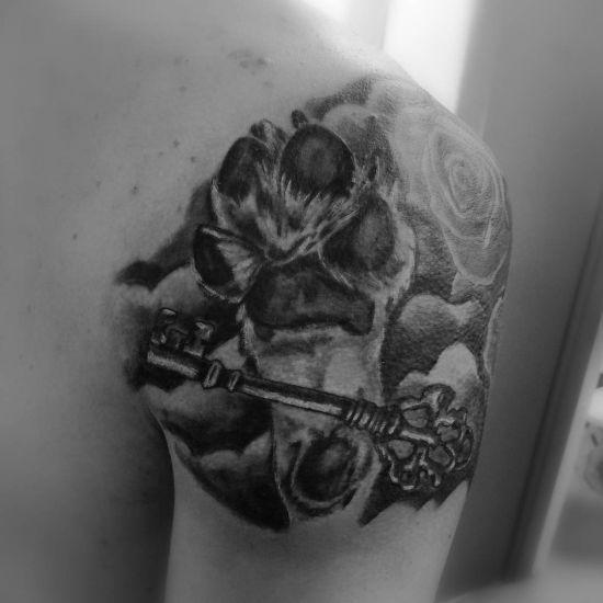 Tatuaje de huella de perro con llave y rosa
