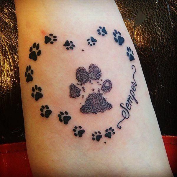 Tatuaje de corazón de huellas con huella central y mensaje o nombre de mascota